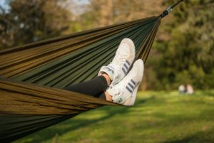persons legs shown, person relaxing in a hammock