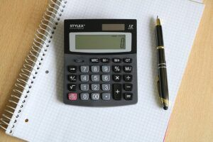 calculator and pen image, signifying the task of calculating the number of BTUS you need for your gas pool heater