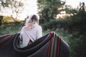 woman uses blanket to warm up outside