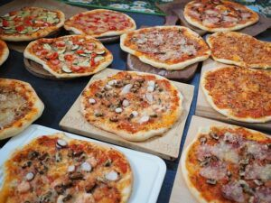 table full of wood-fired pizzas